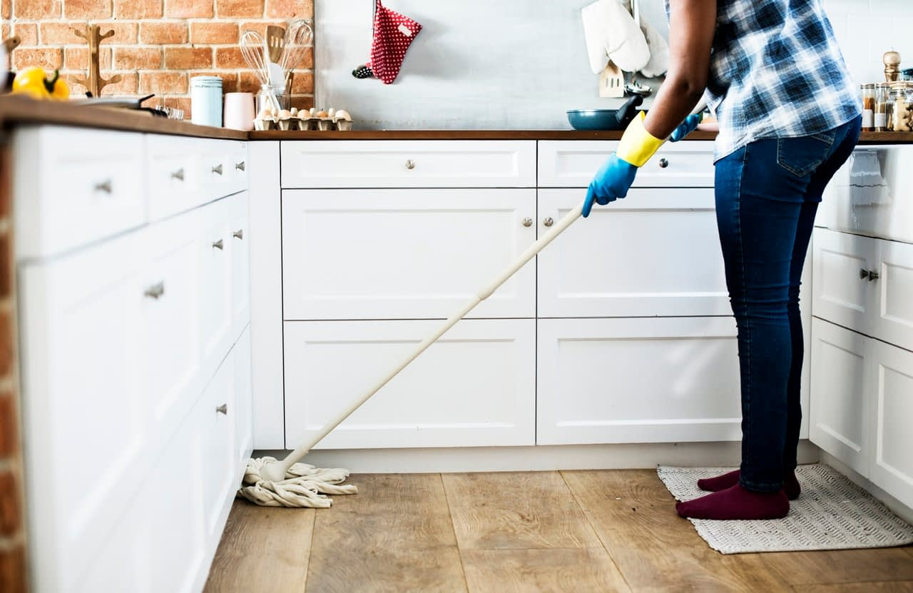 a woman cleaning the kitchen's floor